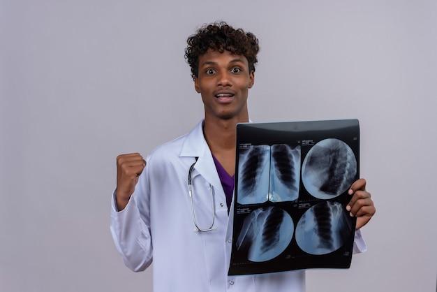 Een jonge knappe donkere mannelijke arts met krullend haar, gekleed in een witte jas met een stethoscoop, voelt zich gelukkig terwijl hij een röntgenrapport toont