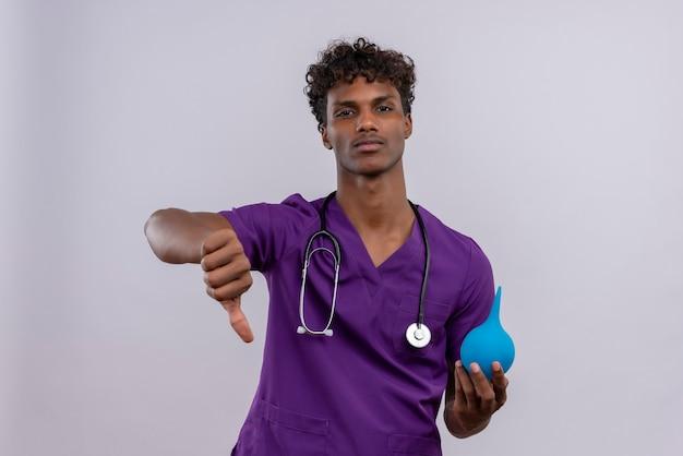 Een jonge knappe donkere mannelijke arts met krullend haar in violet uniform met stethoscoop die duimen naar beneden toont terwijl hij een klysma vasthoudt