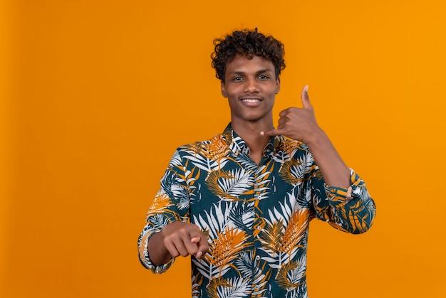Een jonge knappe donkerhuidige man met krullend haar in een met bladeren bedrukt hemd lachend met 'bel me' gebaar