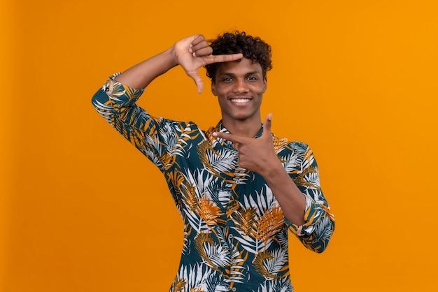 Een jonge knappe donkerhuidige man met krullend haar in een met bladeren bedrukt overhemd en een frame met handen en vingers met een blij gezicht