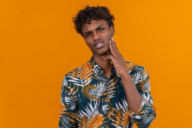 Een jonge knappe donkerhuidige man met krullend haar in een shirt met bladerenprint en een boos gezicht met handen op de wang