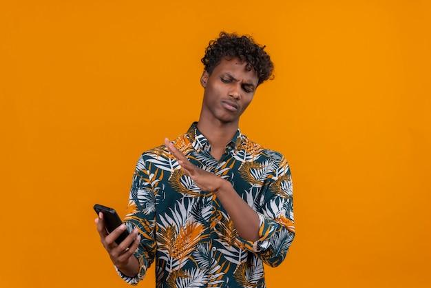 Een jonge knappe donkerhuidige man met krullend haar in een shirt met bladerenprint en een ontevreden uitdrukking op zijn mobiele telefoon