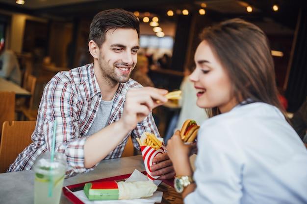 Een jonge, knappe jongen voedt zijn vriendin met een fastfood. een leuk stel in een café.