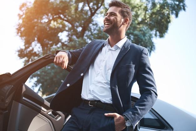Een jonge knappe man in een pak komt uit de auto en lacht