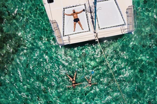 Een jonge knappe man ligt op een jacht in de indische oceaan naast zijn familie die in maskers zwemt. mauritius eiland.