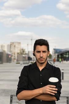Een jonge knappe man staat in een zwart pak op de achtergrond van een kantoorgebouw. hij drinkt zijn koffie uit een hervulbare beker en draagt zorg voor het milieu.