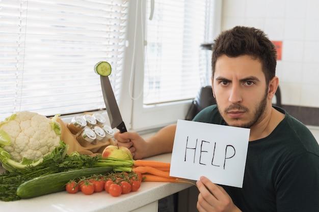 Een jonge knappe man zit in de keuken met een boos gezicht en vraagt om hulp.
