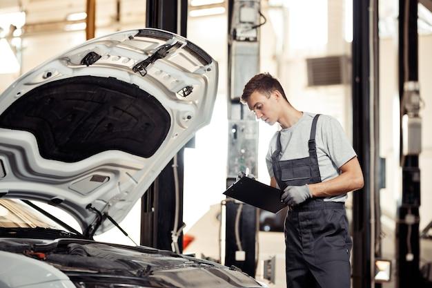 Een jonge knappe monteur controleert alle bugs die hij in een auto heeft gevonden.