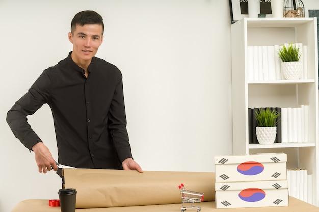 Een jonge koreaanse man in een kantoor pakt een pakje cadeauverpakking voor de post.