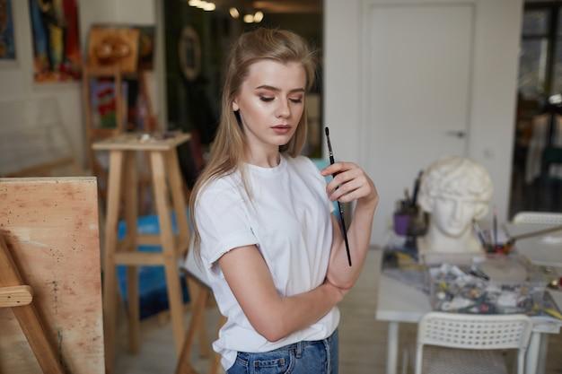 Een jonge kunstenaar staat in een schilderatelier met borstels