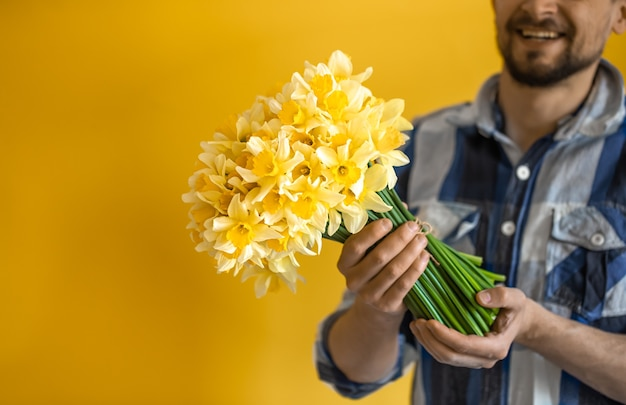Een jonge lachende man met een boeket lentebloemen. het concept van groeten en vrouwendag.