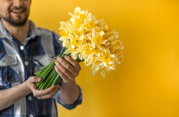 Een jonge lachende man met een boeket lentebloemen