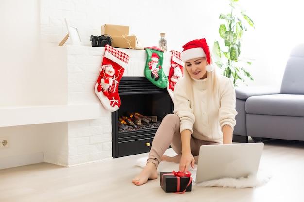 Een jonge lachende vrouw die op eerste kerstdag videogesprek voert op sociaal netwerk met familie en vrienden. Premium Foto