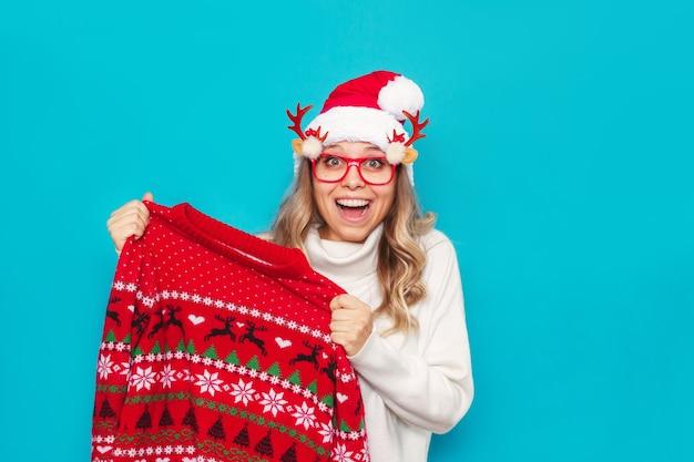 Een jonge lachende vrouw in een witte trui kerstmuts kerstbril houdt een rode trui met herten vast