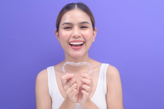 Een jonge lachende vrouw met invisalign beugels in de studio, tandheelkundige gezondheidszorg en orthodontisch concept.
