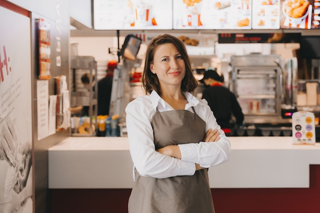 Een jonge lachende vrouw zakenvrouw in een schort staat in een café voor een etalage, haar armen gekruist, kijkend naar de camera.