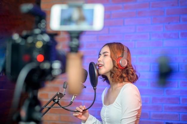 Een jonge lachende zangeres die een koptelefoon met een microfoon draagt tijdens het opnemen van een lied in een muziekstudio met kleurrijke lichten.