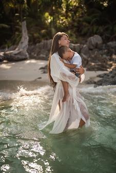 Een jonge lange, langharige brunette, een blond meisje, een moeder, loopt langs de azuurblauwe zee en draagt een kleine, blonde, gelukkige zoon in haar armen. witte katoenen kleding. boho jurk.