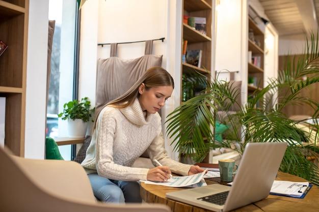 Een jonge langharige vrouw die met documenten en laptop werkt