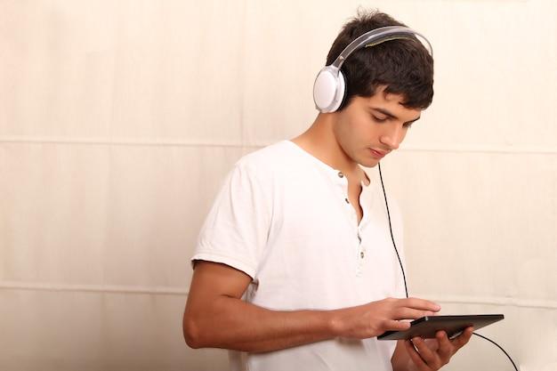 Een jonge, latijnse man die met een tablet-pc speelt