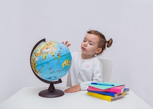 Een jonge leerling bestudeert een wereldbol
