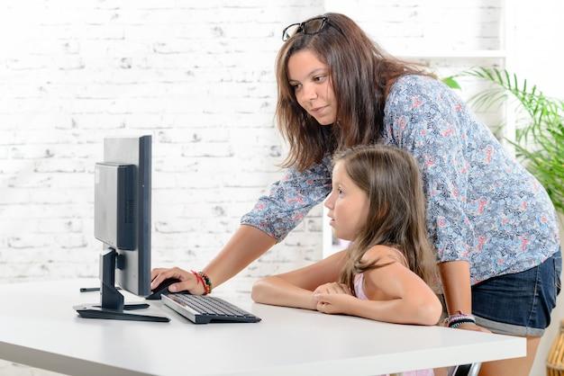 Een jonge leraar helpt een schoolmeisje op een computer