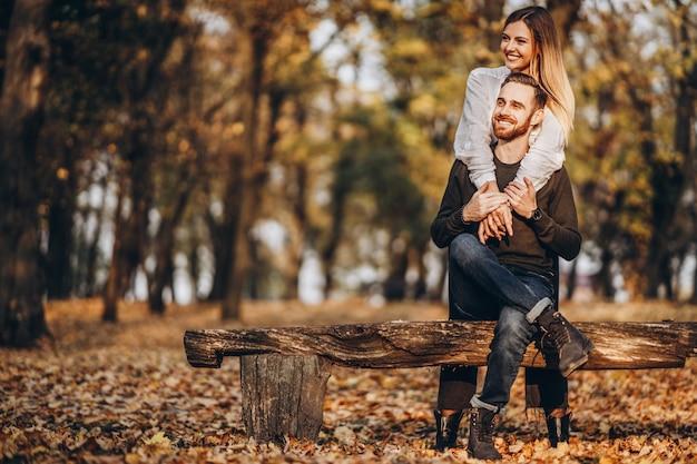 Een jonge liefdevolle paar zittend op een houten bankje in het bos.