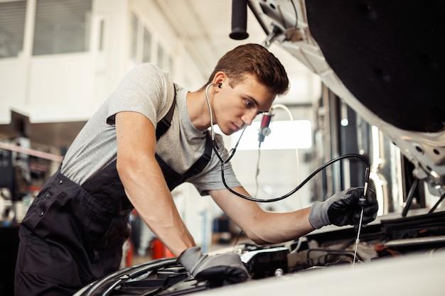 Een jonge maar gekwalificeerde monteur voert een gedetailleerd onderzoek van een auto uit.