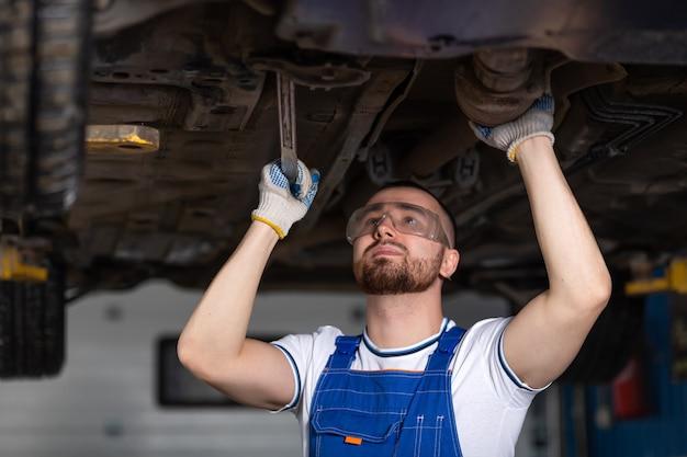 Een jonge man automonteur in overall op zijn werkplek repareert de ophanging van de auto, schijnt een lantaarn op het chassis. concept werknemer bij een autoreparatiewerkplaats, een auto opgeheven op een lift