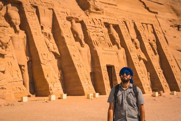 Een jonge man bezoekt de gereconstrueerde tempel van nefertari bij abu simbel in het zuiden van egypte in nubië naast het nassermeer. tempel van farao ramses ii, reislevensstijl