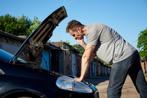 Een jonge man bij de auto met een open kap.