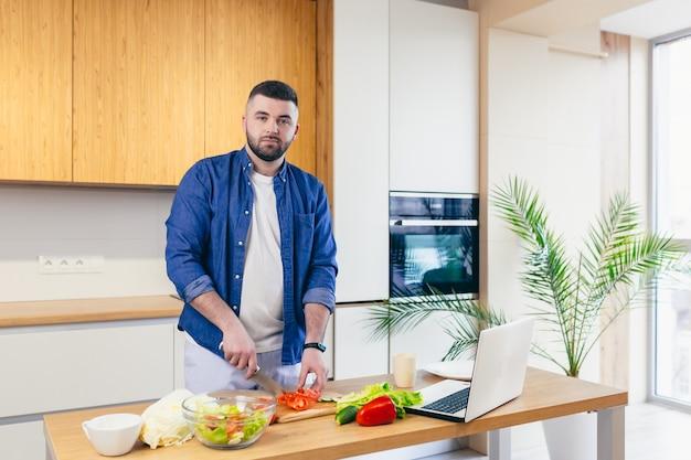 Een jonge man brengt een dag thuis door en bereidt een ontbijt met groenten in de keuken