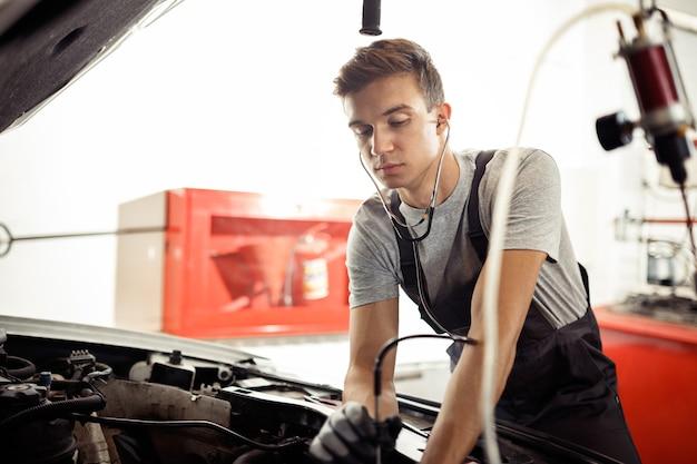 Een jonge man controleert de motor van een auto.