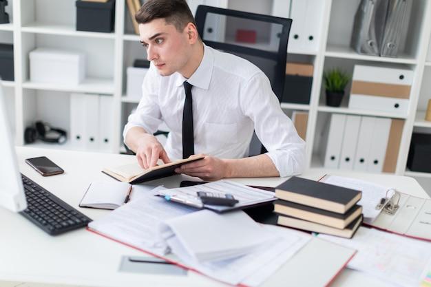 Een jonge man die aan een tafel op kantoor werkt met een boek, documenten en een computer.