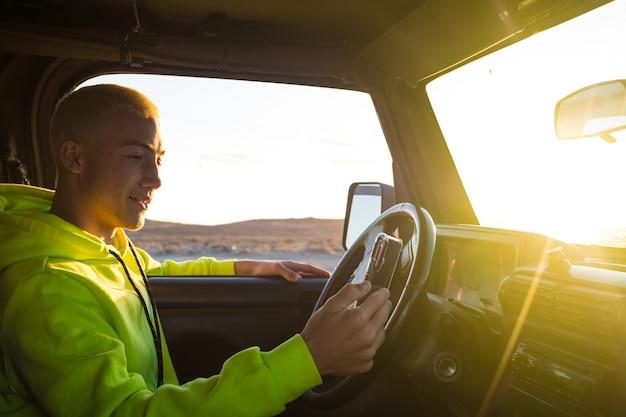 Een jonge man die alleen in zijn auto rijdt en naar de geweldige zonsondergang op de achtergrond kijkt terwijl hij zijn telefoon gebruikt om op kaarten of sociale media te zoeken