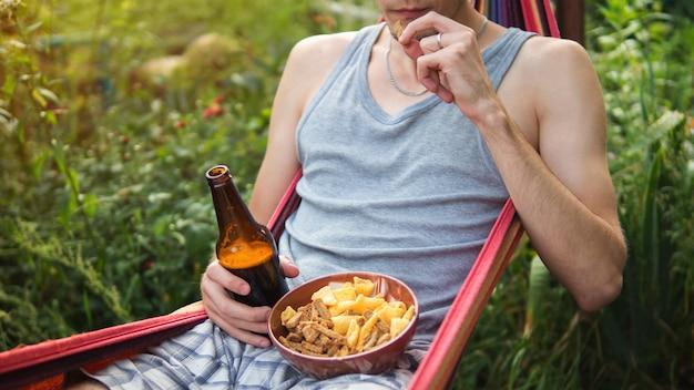 Een jonge man die bier drinkt en crackers eet die op een hangmat in de zomer rusten