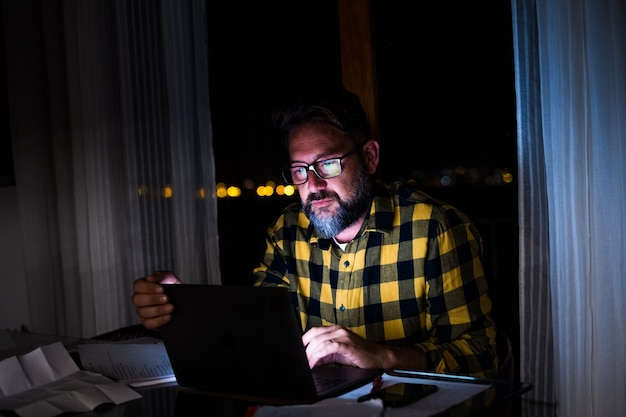 Een jonge man die een laptop gebruikt en 's nachts thuis op een computer werkt. zakenman aan het werk in zijn kantoor