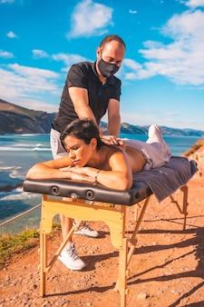Een jonge man die een massage uitvoert in de natuur aan de kust bij de zee, masseuse met een gezichtsmasker in de coronavirus-pandemie