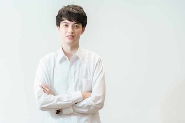 Een jonge man die een wit overhemd draagt en lacht voor een witte achtergrond