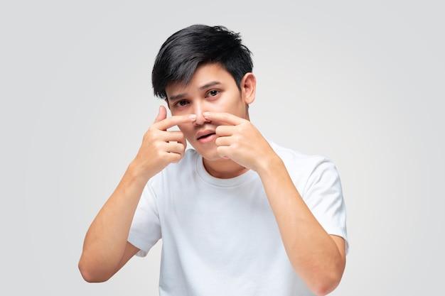 Een jonge man die een wit t-shirt droeg, kneep met zijn hand in een puistje op het puntje van zijn neus.