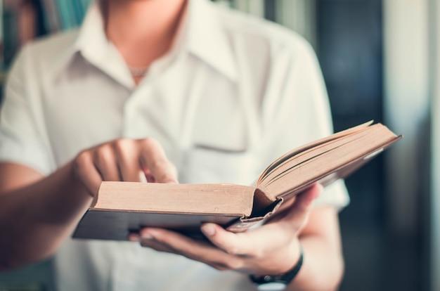 Een jonge man die er goed uitziet door boeken te lezen die op de vensterbank staan