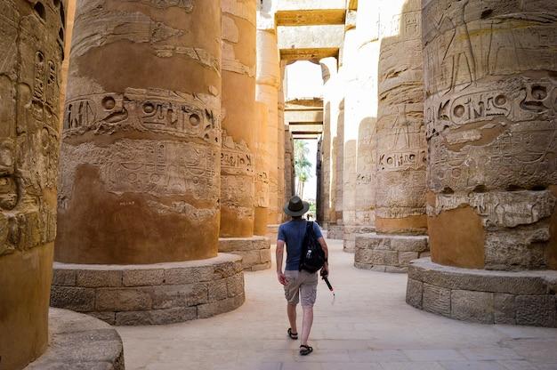 Een jonge man die in een egyptische tempel loopt
