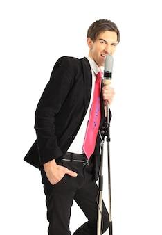 Een jonge man die in een microfoon zingt op een witte achtergrond