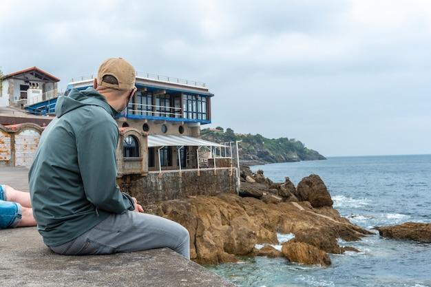 Een jonge man die naar de zee kijkt vanuit de zeehaven van de gemeente lekeitio, golf van biskaje in de cantabrische zee. baskenland