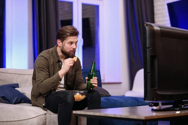 Een jonge man die op de bank in de woonkamer zit, is geschokt door een film op de tv 's nachts.