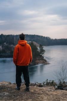 Een jonge man die op de rand van een klif