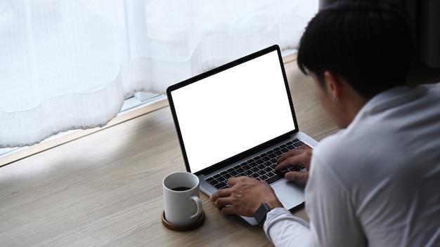 Een jonge man die op houten vloer ligt en thuis op laptop computer werkt.