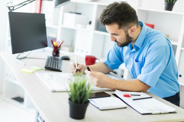 Een jonge man die op kantoor op een computer bureau en werkt met een magnetisch bord.