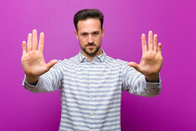Een jonge man die poseerde terwijl hij ontevreden was en de toegang verbood of stop zei met beide open handpalmen