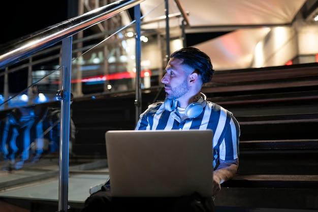 Een jonge man die 's nachts met zijn laptop in een winkelcentrum werkt